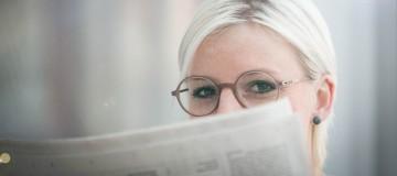 Mitarbeiterin Kathrin Guttmann mit einer Brille von Ray-Ban beim Zeitung lesen